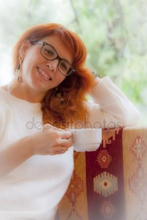 Young smiling girl is drinking tea or coffee — Stock Photo © carlotoffolo #157688058