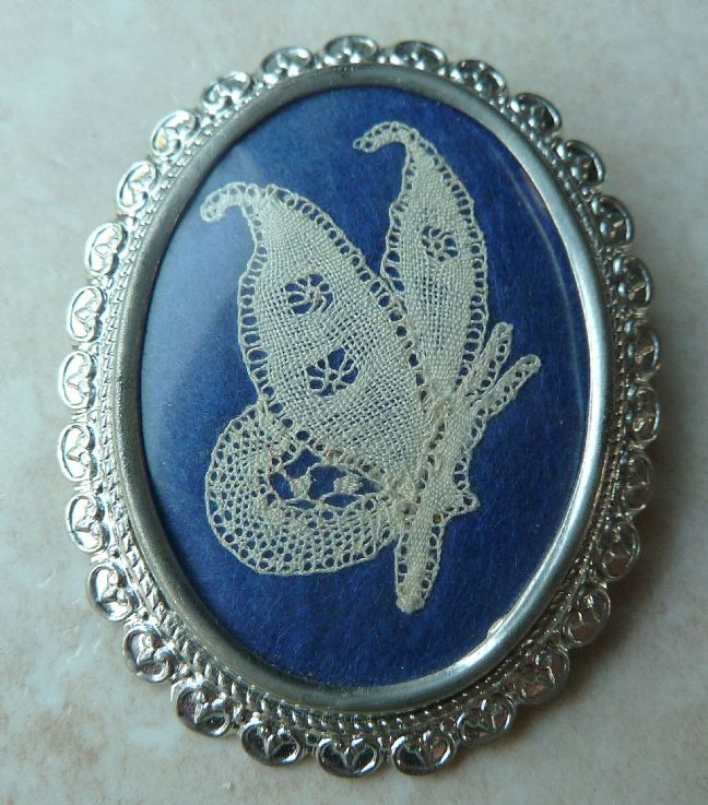 A lovely vintage handcrafted lace work, butterfly brooch manufactured by W A P Watson, under the Exquisite brand.  The brooch features a delicate piece of lacework, shaped in a butterfly design, on a blue material background.  The brooch is set in an ornate silver tone metal frame and is signed ' Exquisite ' to the back .  Circa 1950's - 60's.