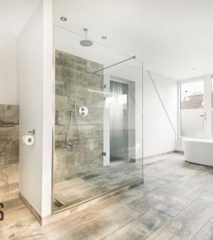 Ruime badkamer met vrijstaand bad en inloopdouche, stucwerk gecombineerd met tegels in houtstructuur, Het Badhuys.