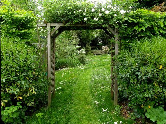 Jardin champêtre et romantique, avec chemins tondus dans la pelouse fleurie. Conception Canopées