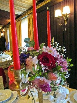 Золотые канделябры с цветочной композицией на столе гостей