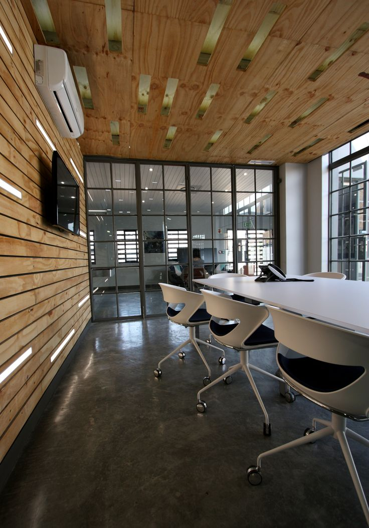 Plywood cladding, recessed lighting with traditional windows creates a light and open boardroom space