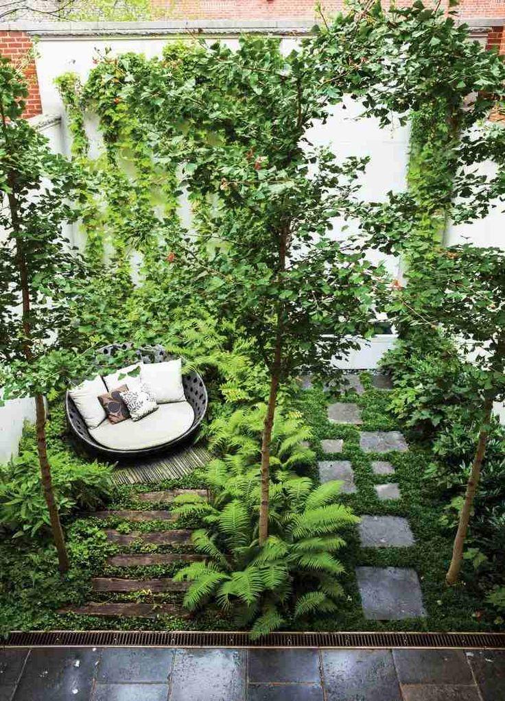 aménagement jardin extérieur avec une végétation luxuriante, un lit de jour moderne et deux petites allées en bois et dalles