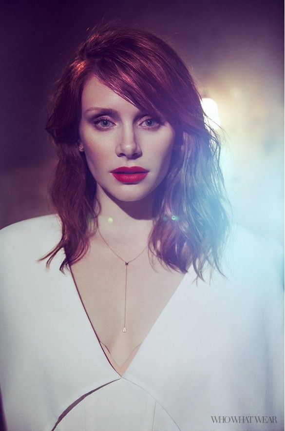 Bryce Dallas Howard wears a bright red lip, white Balmain jacket, a nude dress, and gold jewelry