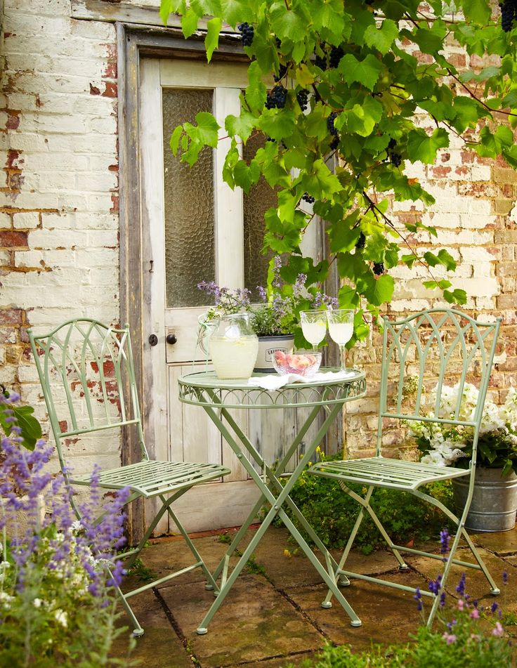 Love the green table and chairs next to the purple flowers