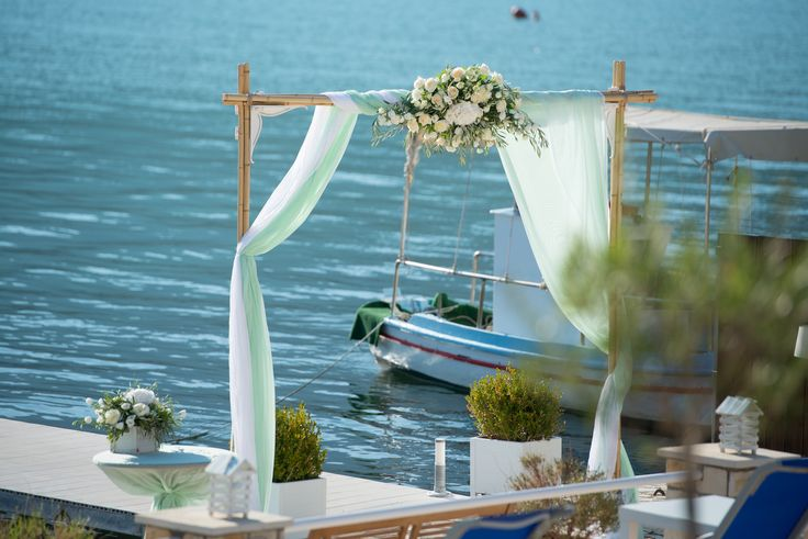 White and sea green wedding arch for ceremony by the sea by Gourioti Flowers