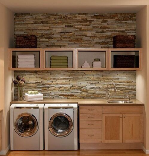 Laundry room lodge style. Natural stone wood floor stainless washer and dryer open wood shelving.