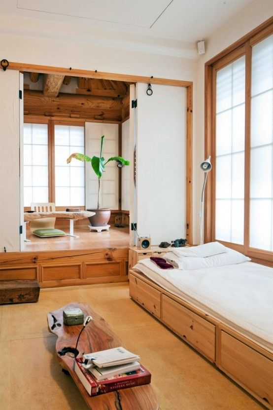 Interior design of a hanok in Seoul, South Korea. This home belongs to Hongnam Kim, an art historian. Her bedroom, pictured, has an adjoining reading room with a raised floor and windows on three sides. It was designed to evoke the feeling of an outdoor pavilion. Read more about her lovely home in the New York Times.