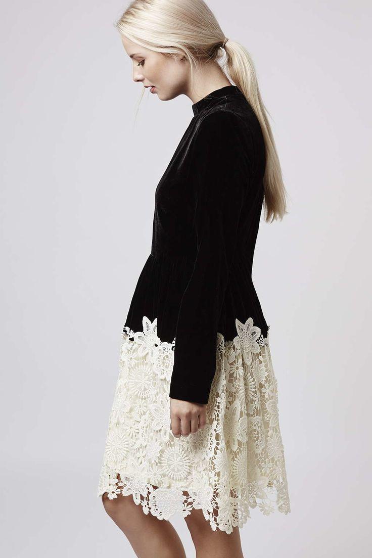 Vestido 'skater' de manga larga y cuello alto en terciopelo negro con falda de guipur en color blanco roto, de Topshop.