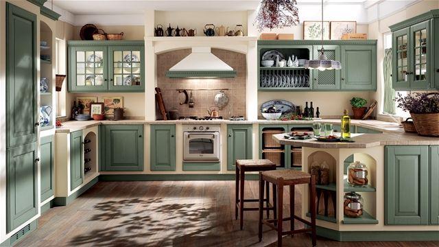"""Si chiama Provenza il sistema di strutture in legno predisposto per gli elementi della cucina Baltimora con ante in Rovere di colore Verde antico. Include una nicchia appositamente progettata per l'area della cottura e si avvale di bellissimi piani in Decorceramica """"Contea"""" con pietra d'Assisi. Una raffinatezza per intenditori. Anta legno Rovere Verde Antico - Scav 256."""