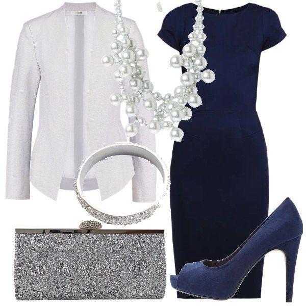 Un tubino blu, dalla linea semplice e a mezze maniche, arricchito dal particolarissimo blazer, color argento, con inserti trasparenti sul retro. Abbiniamo delle scarpe spuntate blu, la clutch color argento glitterata, la collana di perle sintetiche e il bracciale rigido con strass,