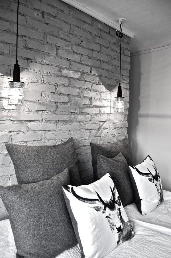 Parede de tijolos com luminárias pendentes combinam com as laterais da cama.