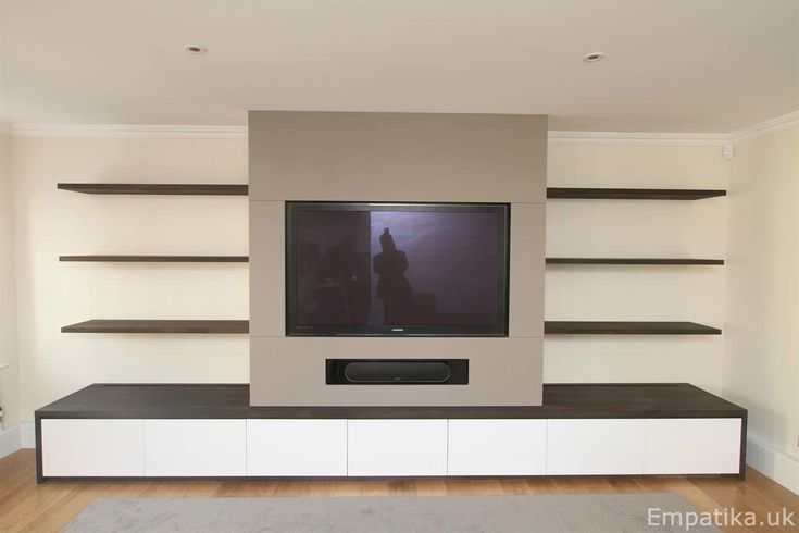 This living room tv unit is made by hand in London using systainably sourced wood. The wood shelves are painted oak veneer and the central section is built around an existing chimney breast. The TV and sound bar are all built into the unit to make them look flush. This unit was designed and built by Empatika bespoke fitted furniture. www.Empatika.uk