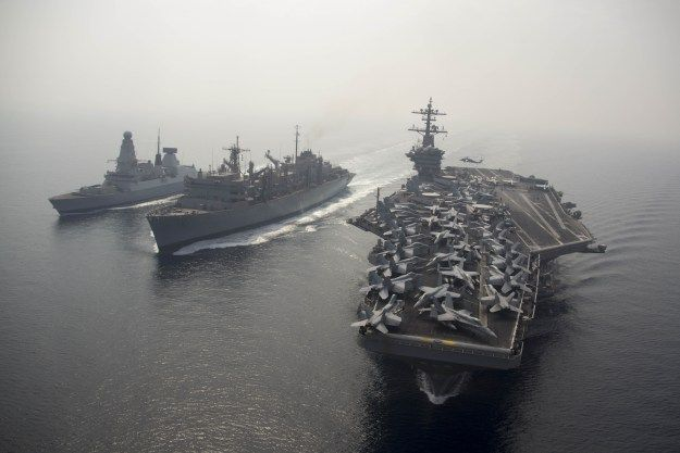 The aircraft carrier USS Theodore Roosevelt (CVN 71) participates in a replenishment-at-sea with the Military Sealift Command fast combat support ship USNS Arctic (T-AOE 8) and the Britizh Royal Navy destroyer HMS Duncan (D 37) on Aug. 26, 2015. US Navy photo.
