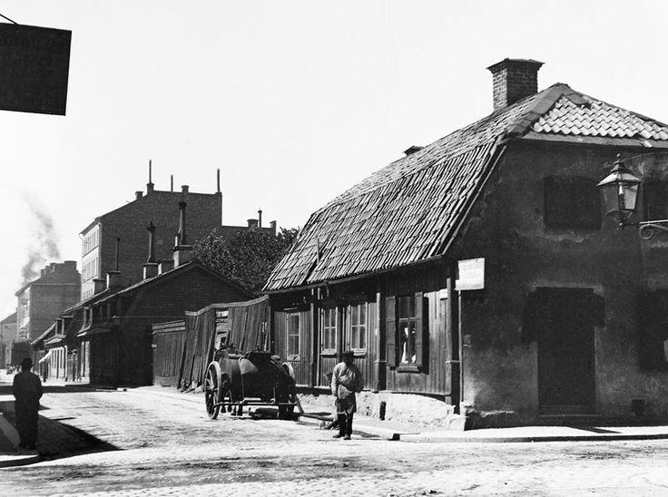 Åsögatan västerut från Södermannagatan. Ett hästfordon står vid Åsögatan 43. Huset revs 1903. Nuv. Åsögatan 139 - Stockholmskällan