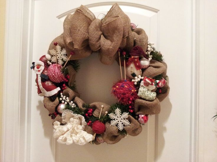 Wreath with antique ornaments, burlap, yarn, and knitting tools