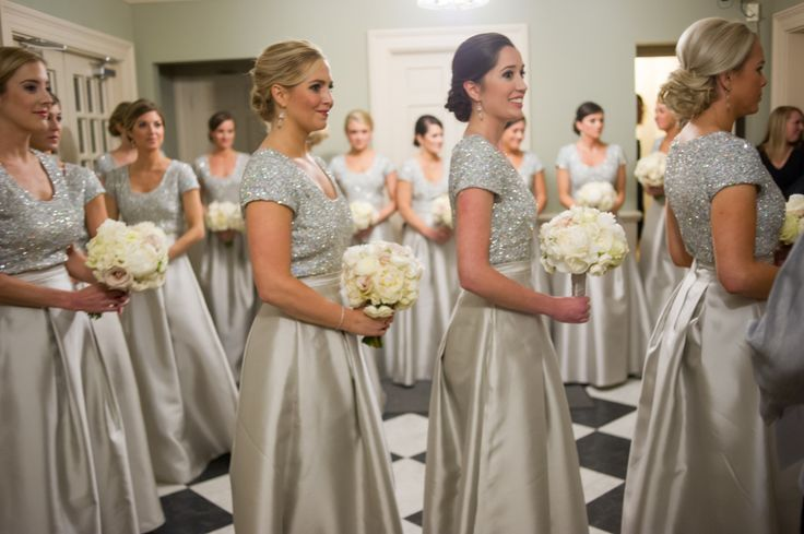 Bridesmaids were dressed for a New Year's Eve celebration in sequined short-sleeve bodices with silver overskirts.They carried bouquets composed of ivory and blush roses. Photography: Liz Banfield and Adrienne Page. Read More: http://www.insideweddings.com/weddings/glittering-gold-new-years-eve-celebration-in-oklahoma-city/614/