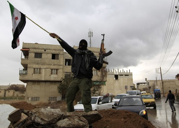 A Syrian soldier who defected to the Free Syrian Army waves an independence flag in the Damascus suburb of Saqba. A small rebel flag at the entrance to Saqba showed that it is no longer under the control of President Bashar al-Assad's forces.  Jan. 27, 2012