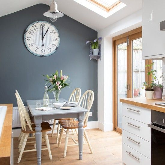 Love this white kitchen with grey feature wall and big clock - the dining room area is perfect.