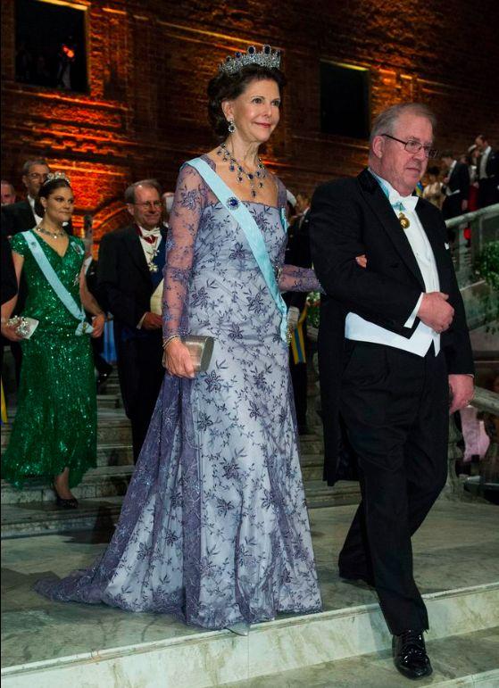 Drottning Silvia, Nobel 2012  Drottningen bär en ljuslila klänning med spets och broderier. Diadem, halsband och örhängen är de så kallade Leuchtenbergska safirerna.