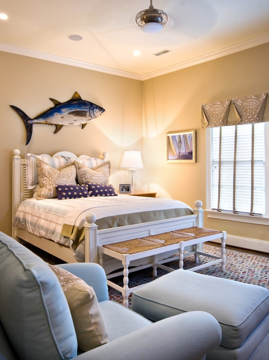 love the fish hanging above the bed . cute coastal cottage look .