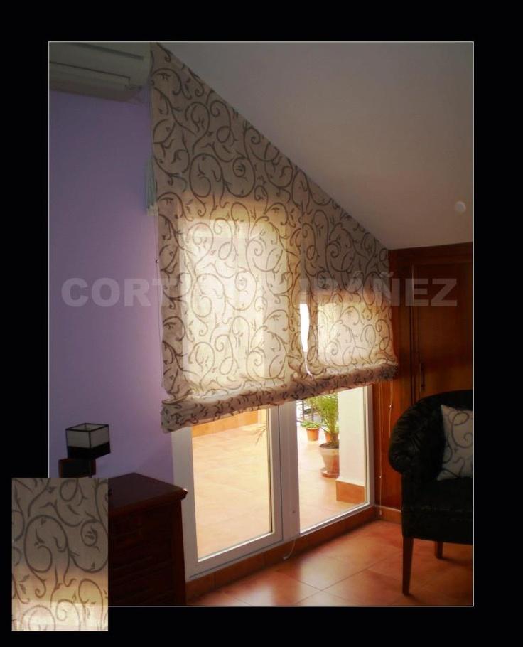 """F2 Estores """"Noche y día"""" instalados en un dormitorio con techo inclinado y cojines a juego. 2 estores """"Romanos"""" en tela de Foscurit para que no pase la luz y 2 estores """"Paqueto"""" que dejan pasar la luz y la matizan."""