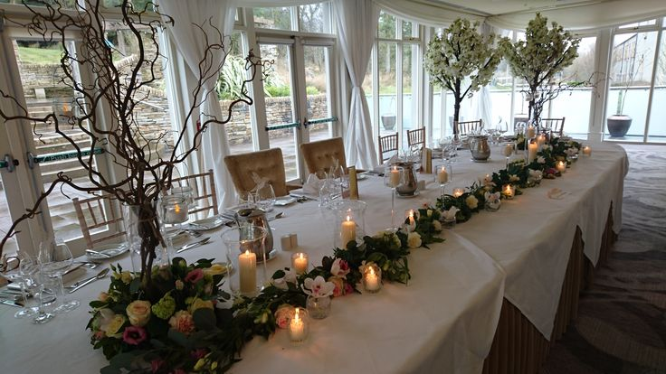 Top table decorations with garlands of fresh flowers and candlelight