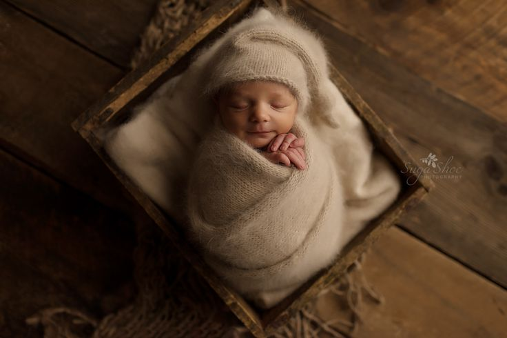 Newborn pose Baby wearing Creamed it hat and matching frappe sleeping in antique crate on top of cream blanket
