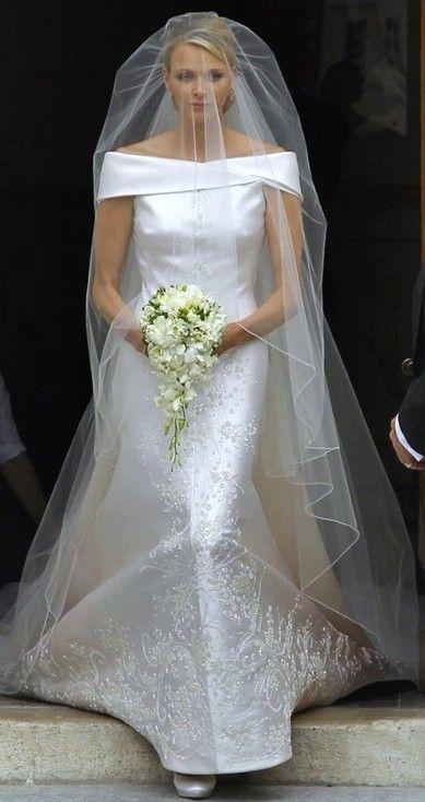 O casamento de Charlene, Princesa de Mônaco. O vestido de noiva tem decote ombro a ombro e detalhes bordados que vão subindo da barra ao topo.