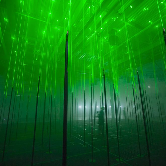 "Installation designed by studio Marshmallow Laser Feast for the STRP Biennale in Eindhoven. ""Forest"" is a giant, immersive laser installation covering almost 450 sq m  featuring 150 musical ""trees"" made of rods and neon lights."