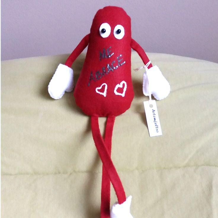 """O bonequinho em feltro """"Me abrace"""" é uma ótima opção de presente para o dia dos namorados. Todo em feltro na cor vermelho com mãozinhas e pezinhos brancos. Tem a frase """"Me abrace"""" e dois coraçõezinhos gravados com tinta 3D e pernas compridas. Mede 32 cm x 8 cm x 6 cm."""
