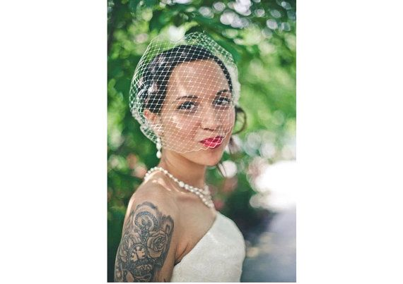 This bridal birdcage veil in an ivory color would be a lovely addition to accent your bridal hair-do. It is attached to two bobby pins with ivory