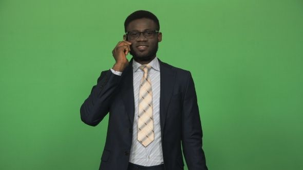 Young African Man Answering Phone Call by FrameStock Young african businessman in formal suit answering and talking phone isolated on green background. Then turn to camera looking and smile More tags male, successful, talking phone, business, worker, communication, suit, lifestyle, african, black, ethnic, african american, green screen, businessman, connection, phone, young, technology, chromakey, l