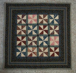 Mini pinwheel quilt in blues, tans, reds and golds