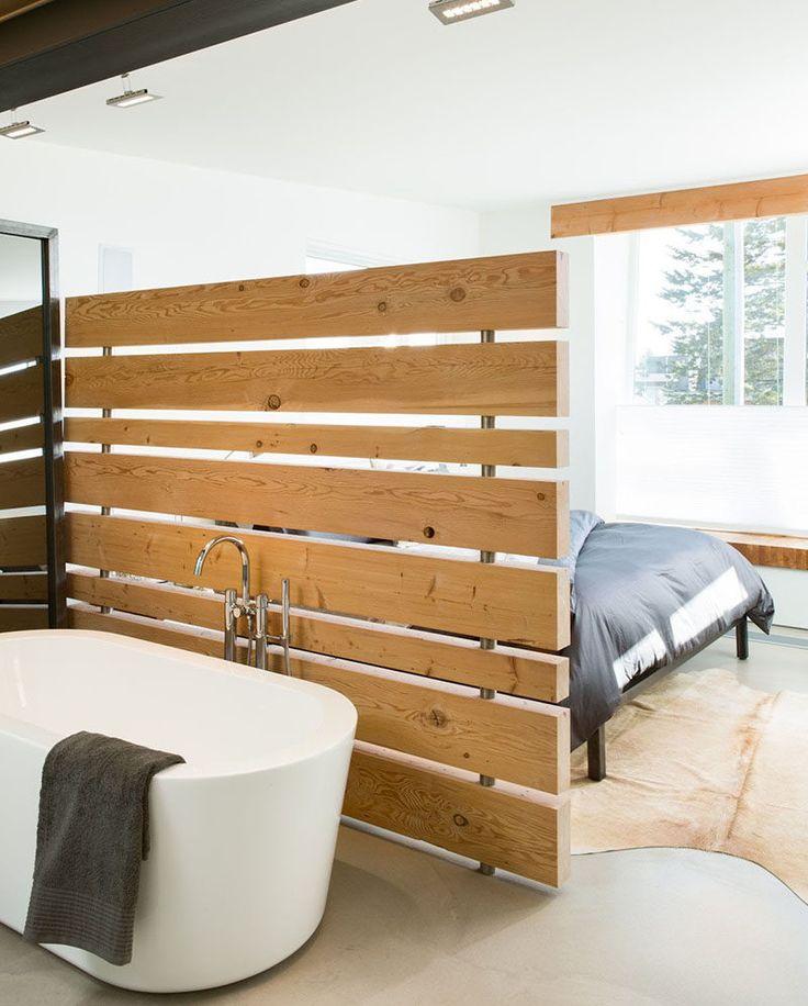 15 ideias criativas para Divisórias // Uma parede de painéis de madeira separa a banheira da cama em uma das casas mais verdes do Canadá.