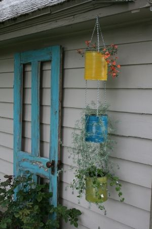 Tin can vertical plant hanger and rustic painted wooden screen door. I