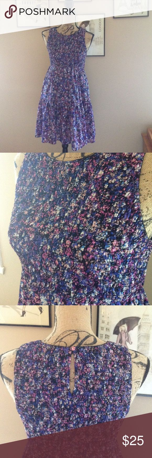A purple, pink, white, and black printed dress A puckered elastic bodice. Entire dress is lined with black polyester. Sleeveless. 100% polyester. Skirt part had a ruffled bottom that is 11 inches long. Only worn twice. Vera Wang Dresses Midi