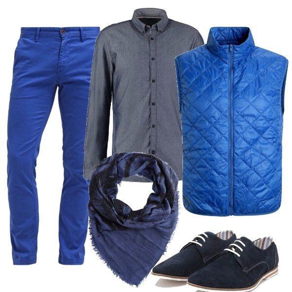 Belle tonalità di blu nei pantaloni di cotone, e nel leggero gilet imbottito, più serio il colore della camicia con bottoni nel colletto e le scarpe stringate, completa un foulard.
