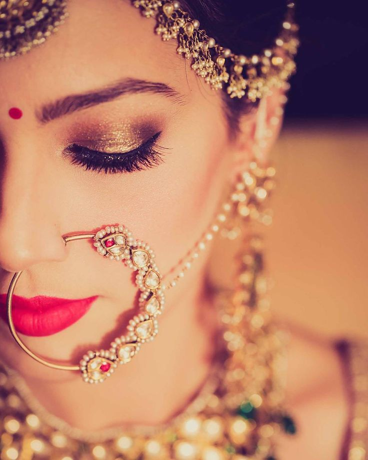 Indian bride wearing bridal jewelry. Smokey eye makeup. Red lips. Nose ring. Indian Bridal Hairstyle. Indian Bridal Makeup. Indian Bridal Fashion. Bridal Photoshoot.