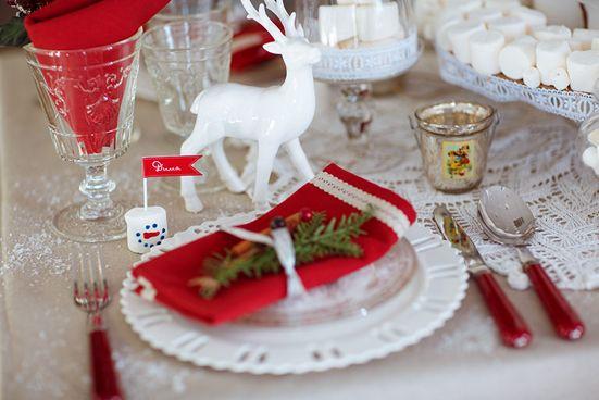 Фарфоровая посуда с ажурными окантовками, кружевные салфетки, будто снежинки. Фарфоровые олени среди посуды, будто герои из сказочного леса. Стеклянные тарелочки, бокалы, бонбоньерки и клоши словно сделаны изо льда. «Снеговички» из сладкого маршмеллоу - отличная альтернатива традиционному держателю для именных карточек. Просто вставьте в зефир зубочистку с флажком и напишите имя гостя. И добавьте цветовой акцент – красные салфетки, столовые приборы с красными рукоятками. www.in-lavka.ru