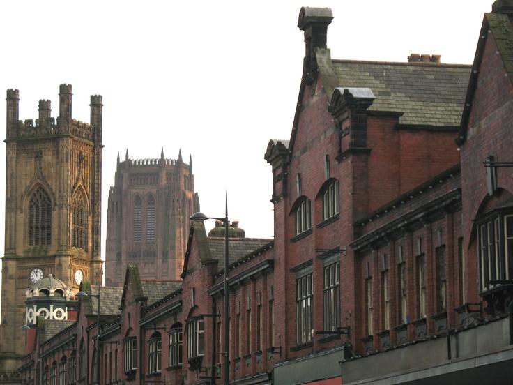 Een typisch industrieel Engelse straat in het centrum van Liverpool met bakstenen huizen en de kerktorens van St. Luke en van de Anglicaanse kathedraal.