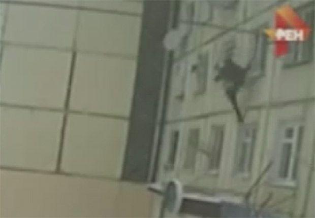Flagrada por câmeras de segurança na cidade de Tulun, a mulher, que não teve seu nome divulgado, é vista pendurada na janela, antes de cair quase 4 metros na escada do prédio.