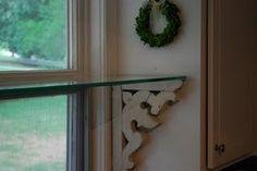 Build kitchen window shelf held up with antique corbels.
