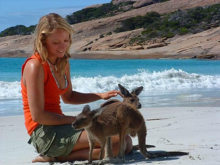 Girl with joey (kangaroo) on beach, near Esperance, in Western Australia.   Kangaroos may often be seen on the white sand beaches located near Esperance on the Southern Ocean coastline in Golden Outback