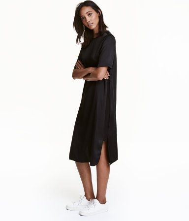Black. Straight-cut, calf-length dress in woven fabric with a slight sheen and heavy drape. Opening at back of neck with button, short sleeves, and matte