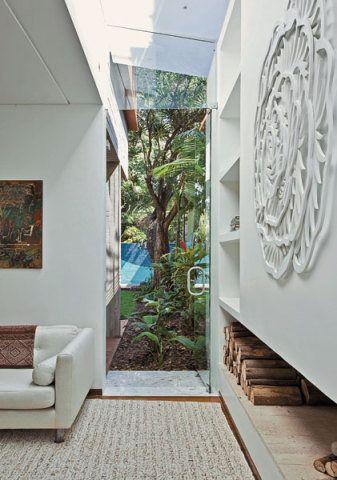 Nas duas pontas da lareira, portas de vidro dão passagem para os jardins lat...