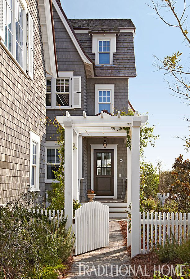 An arbor covered walkway leads to the door of this stunning beach home. - Photo: Colleen Duffley: