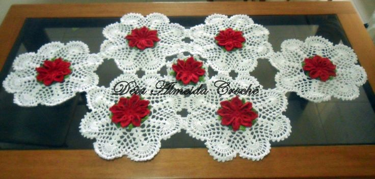 Caminho de mesa em crochê com flores em vermelho, folhas verde multicolorido e fundo em fio branco.  Pode ser feito em outras cores e tamanhos, de acordo com sua necessidade.