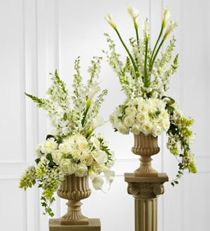 White roses, open cut calla lilies, peonies, Star of Bethlehem, delphinium, larkspur, hydrangea, and snapdragon are arranged with interest and style to towering perfection. Seated in a classic resin urn upon a 3-foot pedestal, this arrangement will add to the joy and beauty of the day. Visser's florist