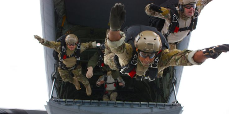 Explosive Ordnance Disposal 1st Class Andrew McCabe, assigned to Explosive Ordnance Disposal Mobile Unit (EODMU) 8, leads the exit from the cargo door of a C-130 during free fall training at Naval Station Rota, Spain.